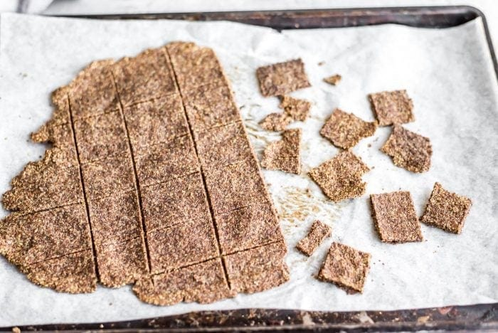 Easy flax crackers on a baking tray with parchment paper.