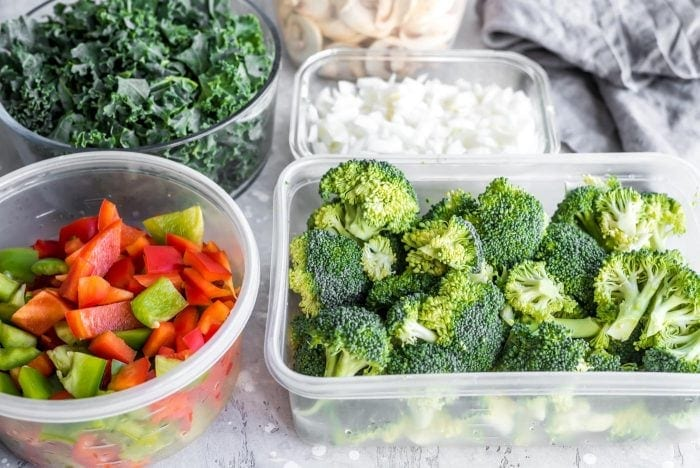 Chopped broccoli, peppers, onions, mushrooms and bell peppers in food storage containers.