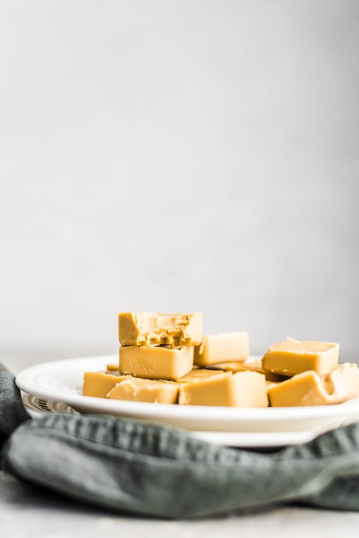 Sunbutter vegan freezer fudge recipe on a white plate with one piece with a bite out of it.