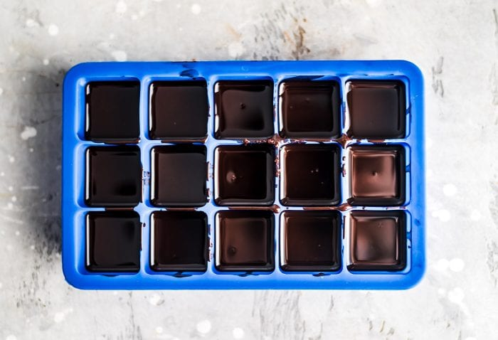 Melted coconut oil chocolates in a blue silicone ice cube tray for making vegan chocolates.