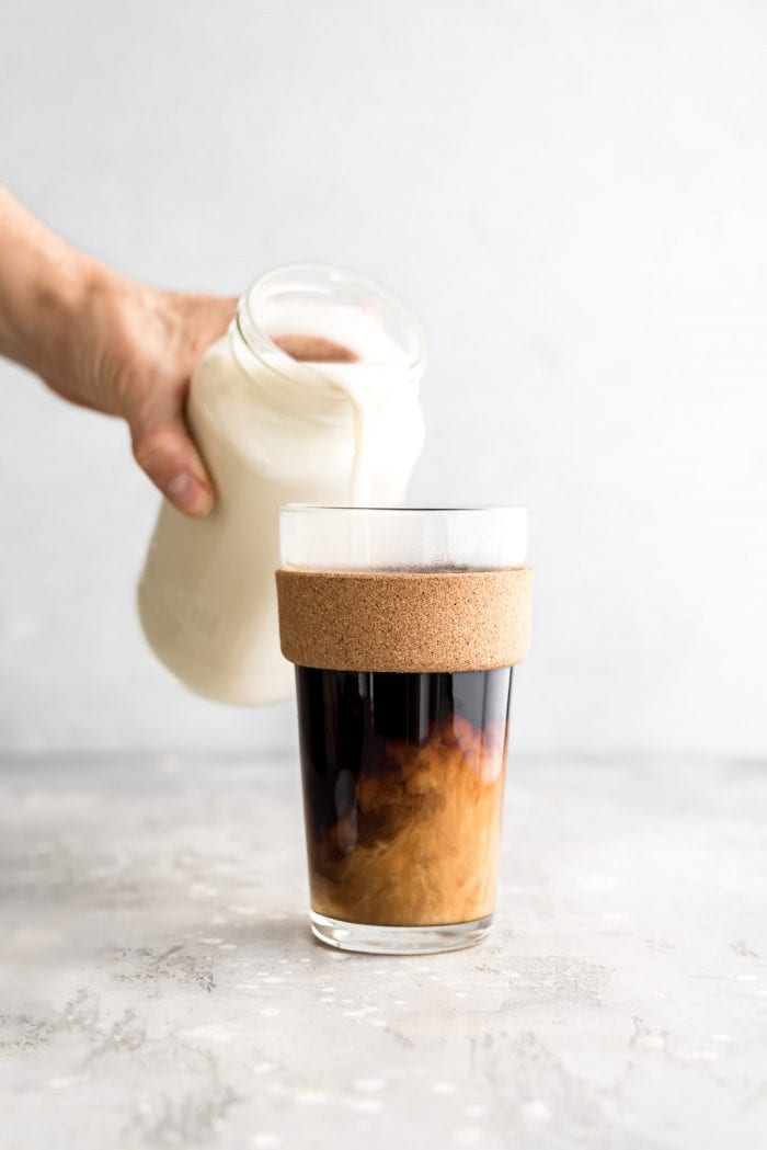 Pouring homemade oat milk into a glass of hot coffee.