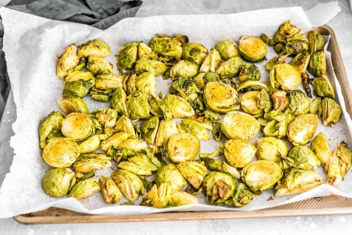 Roasted brussel sprouts on a baking tray for vegan meal prep.