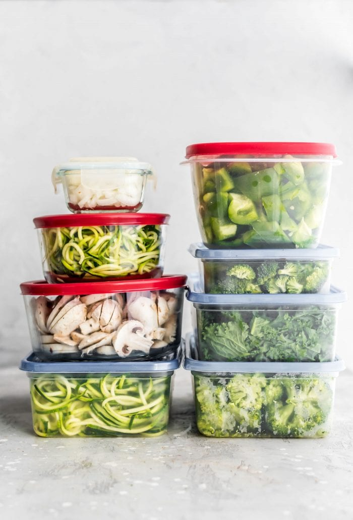 Food storage containers full of fresh chopped veggies for vegan meal prep.