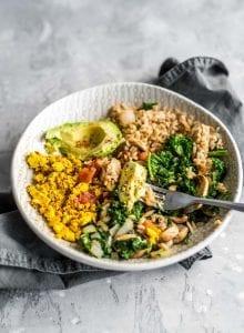 Avocado, mushrooms and kale, tofu scramble and brown rice in a bowl.