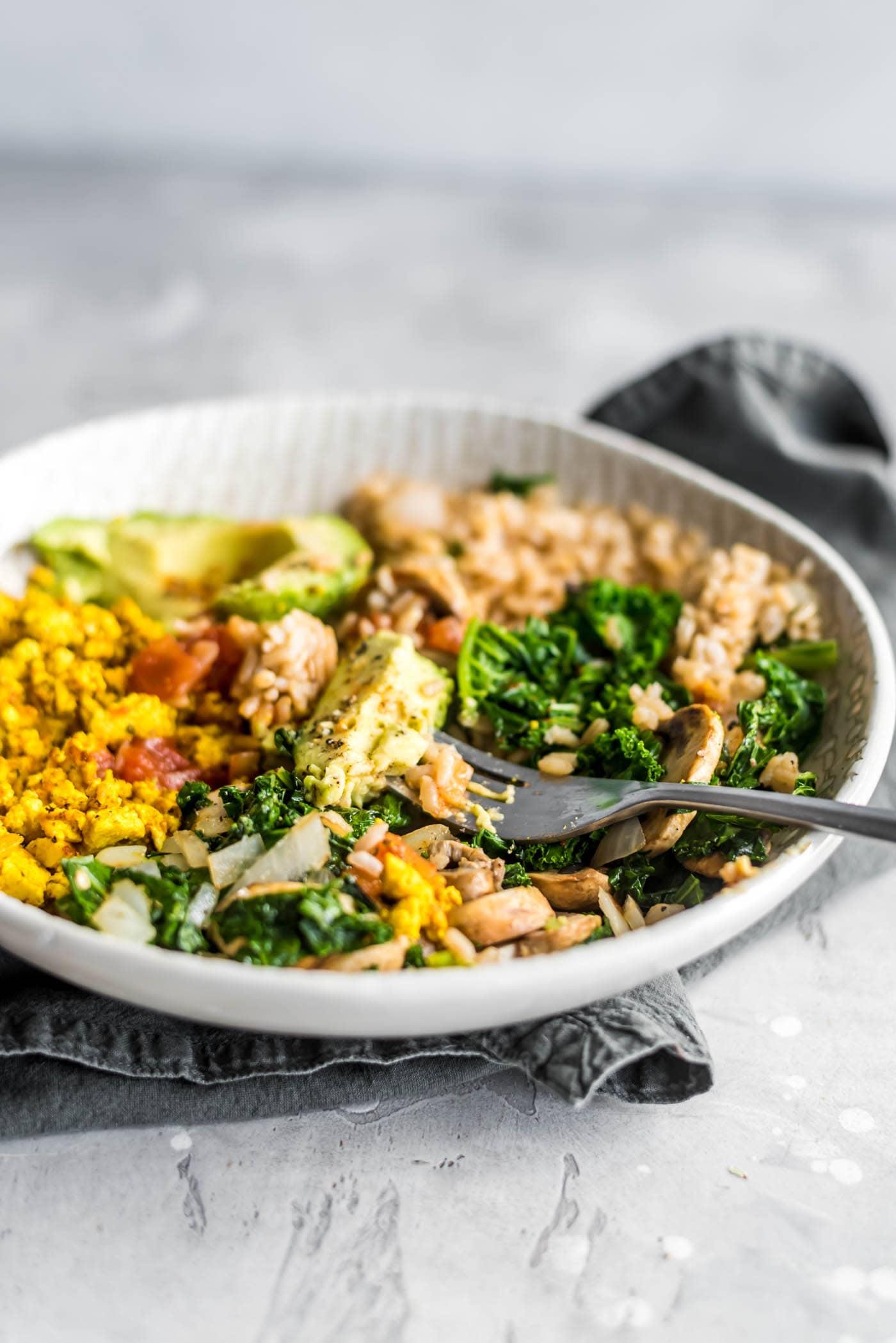 Avocado in a savory vegan breakfast bowl with kale, tofu scramble, rice and salsa.