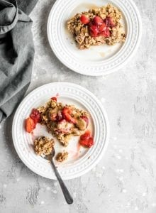 Easy Vegan Apple Cinnamon Baked Oatmeal on a plate with strawberries and almond butter.