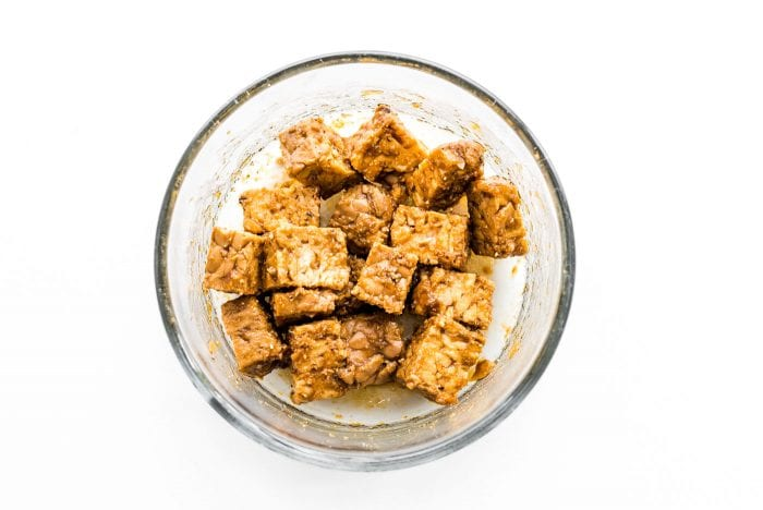 Marinated tempeh in a small glass dish.