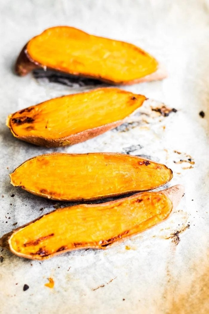 Roasted sweet potatoes on a baking tray - Vegan Essentials.