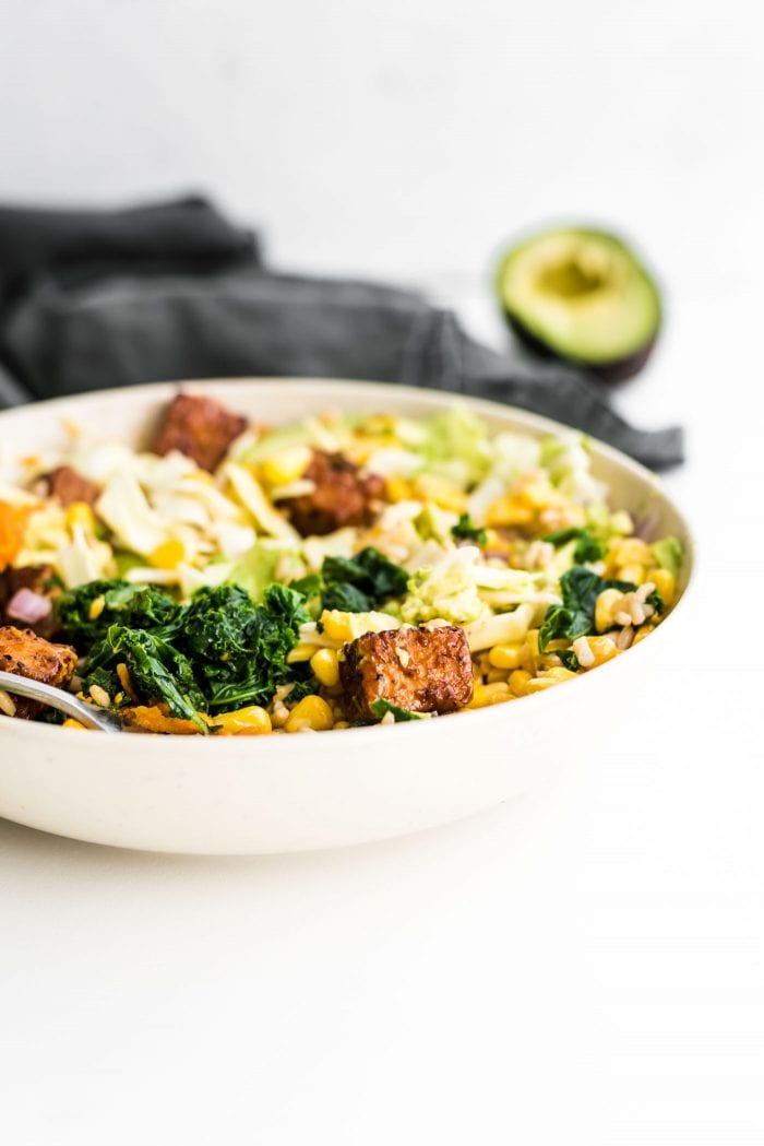 BBQ tempeh and kale in a bowl with coleslaw and avocado.