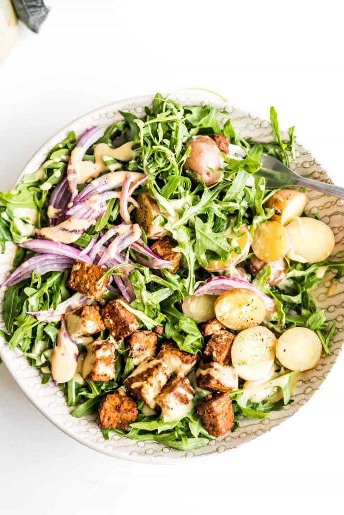 Red onion, tempeh and boiled potato arugula salad with dijon dressing.