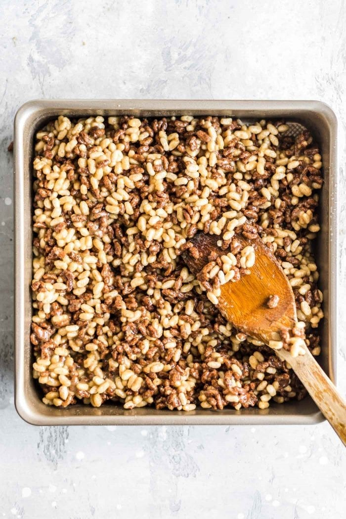 Mixture of brown rice cereal being pressed into a baking pan with a spatula.