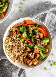 Overhead shot of a bowl of veggie stir fry with brown rice and tempeh.