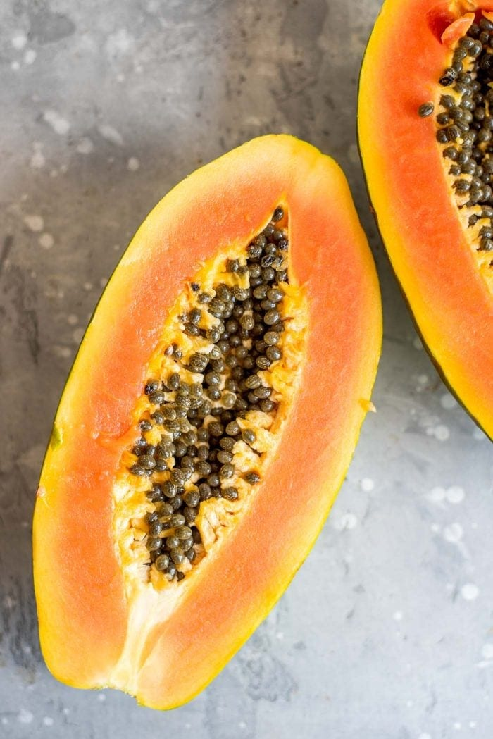 Half of a fresh cut papaya with seeds.