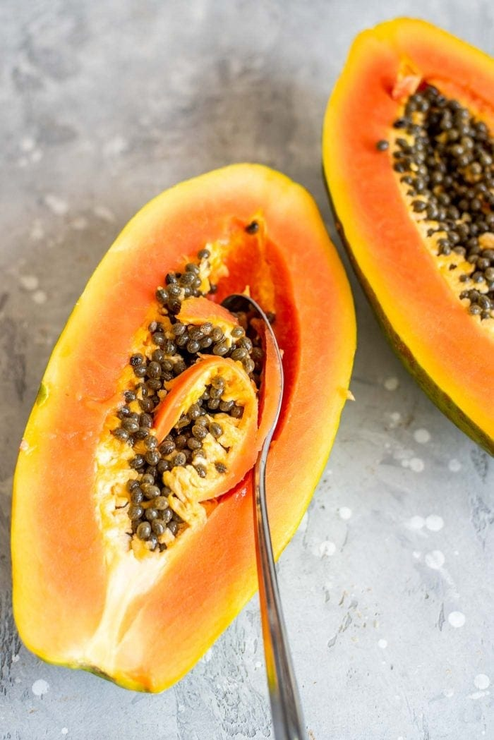 Spoon scooping the seeds out of a fresh cut papaya.