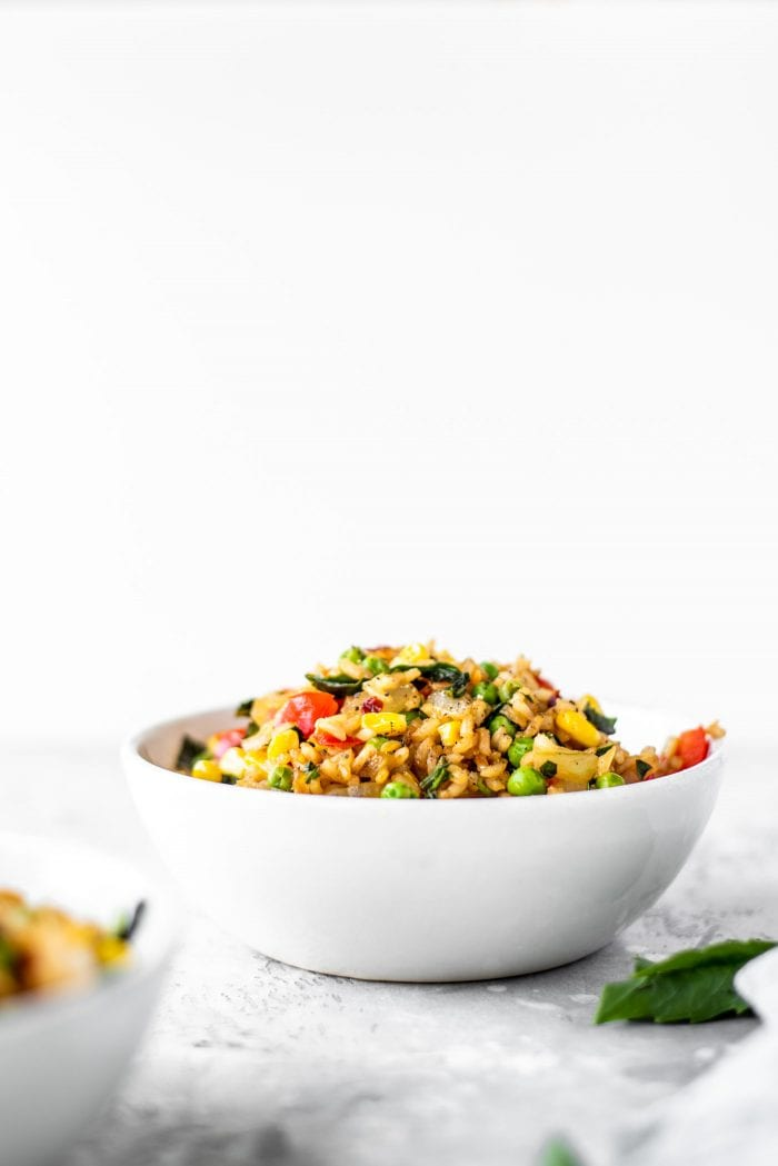 A white bowl of healthy fried rice against a white background.