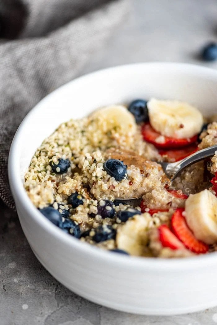 Easy breakfast quinoa in a white bowl with hemp seeds, almond butter, berries and banana.