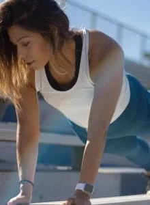 Fit young woman doing a plank on some bleacher benches.