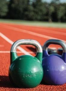 Two kettlebells sitting on a running track.