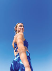 Fit woman in blue workout gear looking back over her shoulder.