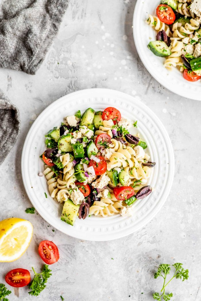 Oil-free and vegan Greek pasta salad on a small white plate with lemon and tomatoes.