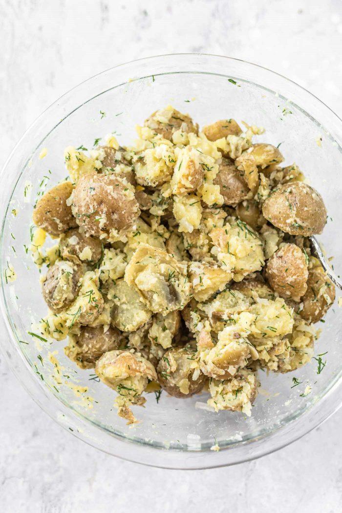 Dijon potato salad in a large, glass mixing bowl.