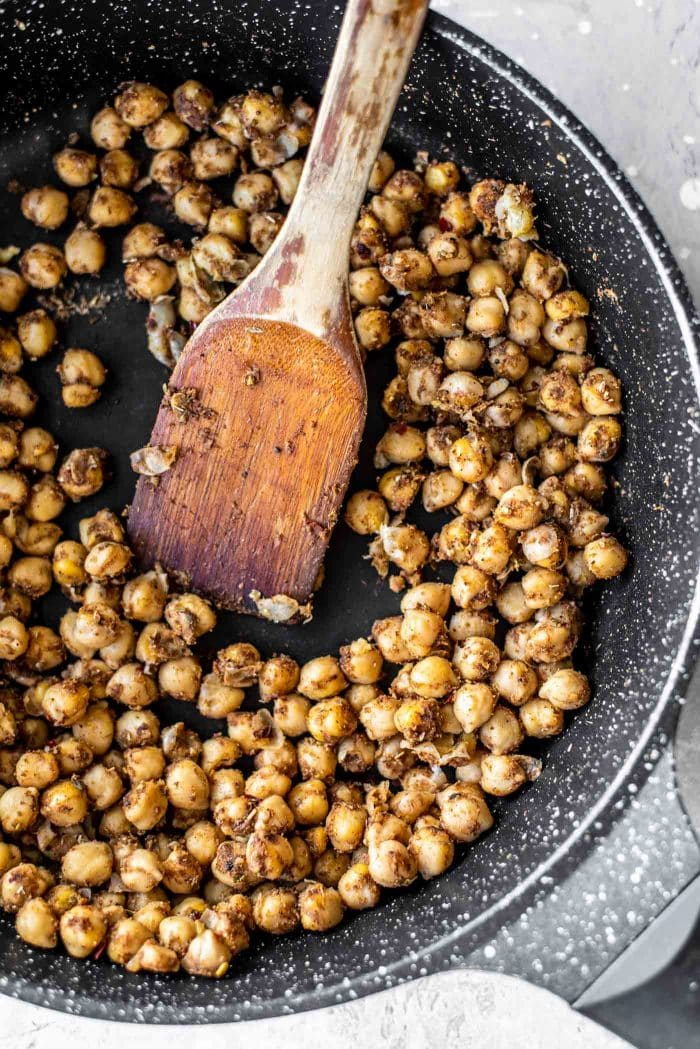Shawarma chickpeas with spices in a black skillet.