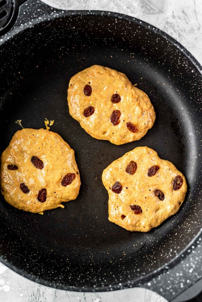 Vegan carrot cake pancakes with raisins in a black skillet.