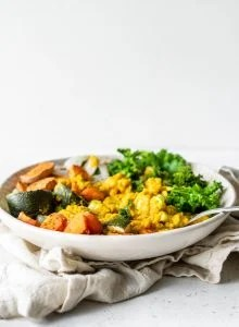 Bowl with lentils, roasted vegetables and kale against a white background.