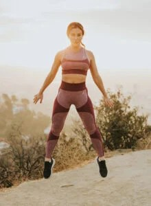 Fit woman jumping in the air on a dirt road.