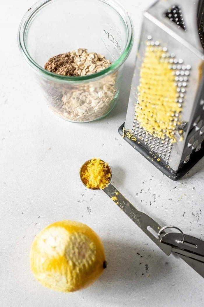 Lemon being grated to make fresh lemon zest.