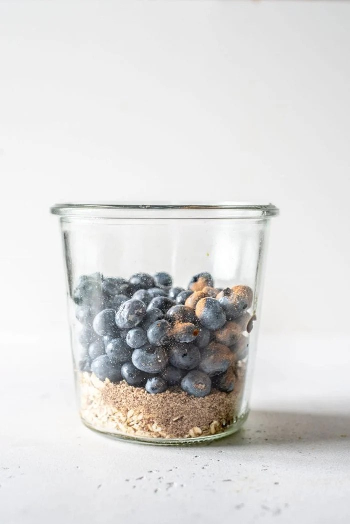 Oats, flax, lemon and blueberries in a glass jar.