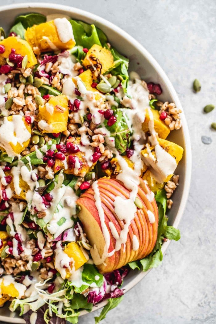 Close up of a colorful squash and farro salad with apple and pomegranate.