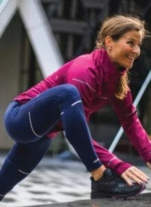 Fit woman in blue tights and a pink jacket stretching before a run.