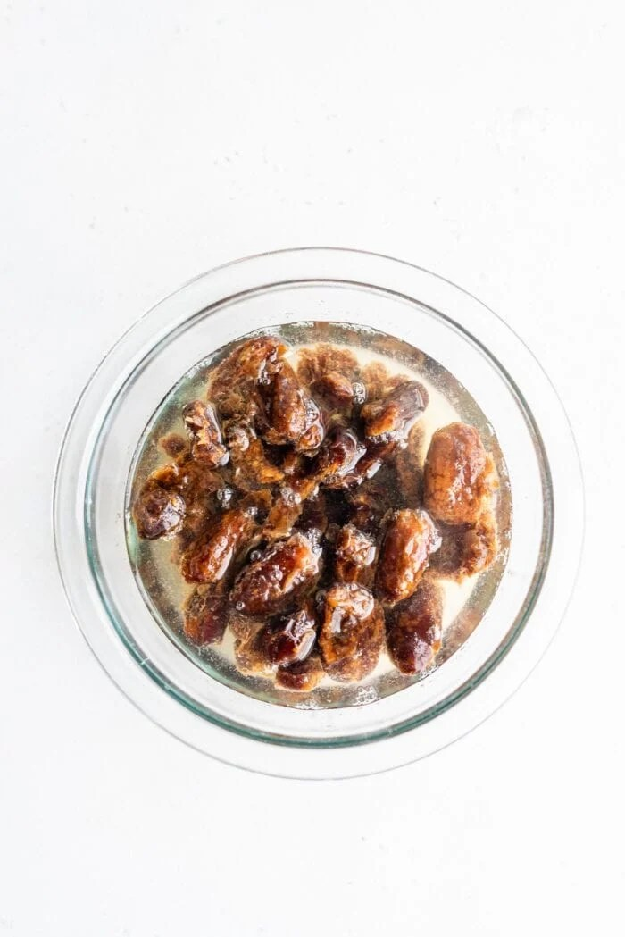 Pitted dates soaking in hot water in a glass bowl.