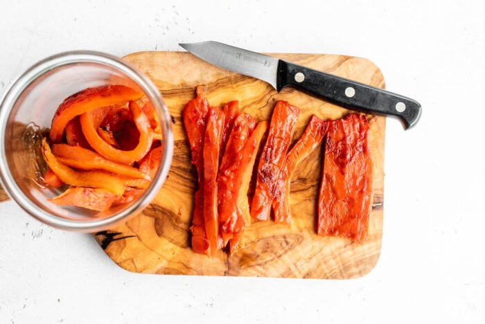 Sliced roasted red peppers on a cutting board.