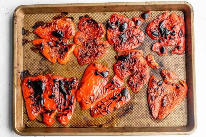 Roasted red peppers on a baking tray.