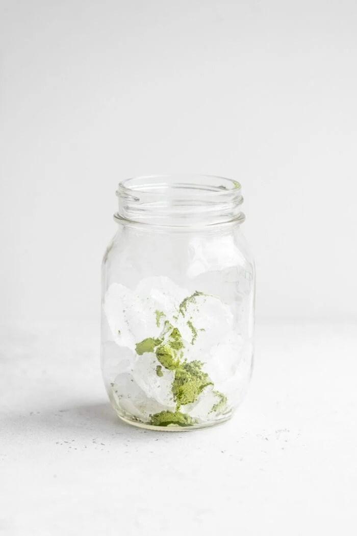 Ice and green tea matcha powder in a small glass mason jar.