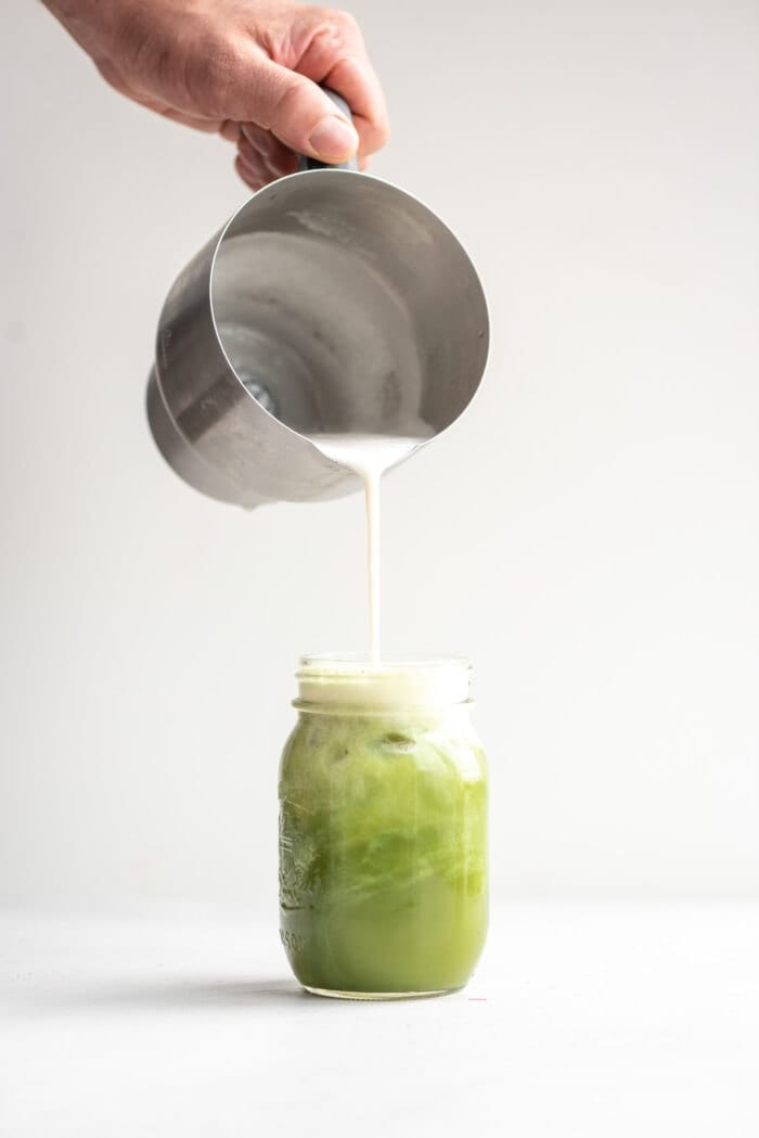 A hand pouring frothed almond milk into an iced matcha.
