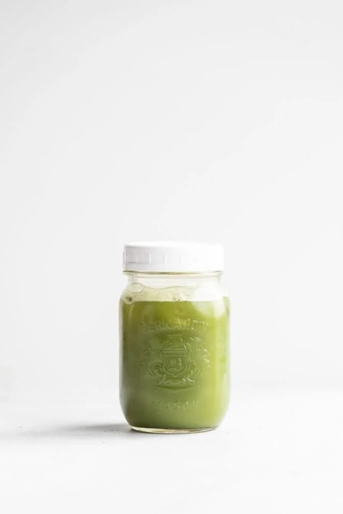 Iced green tea matcha in a glass mason jar with a white lid.