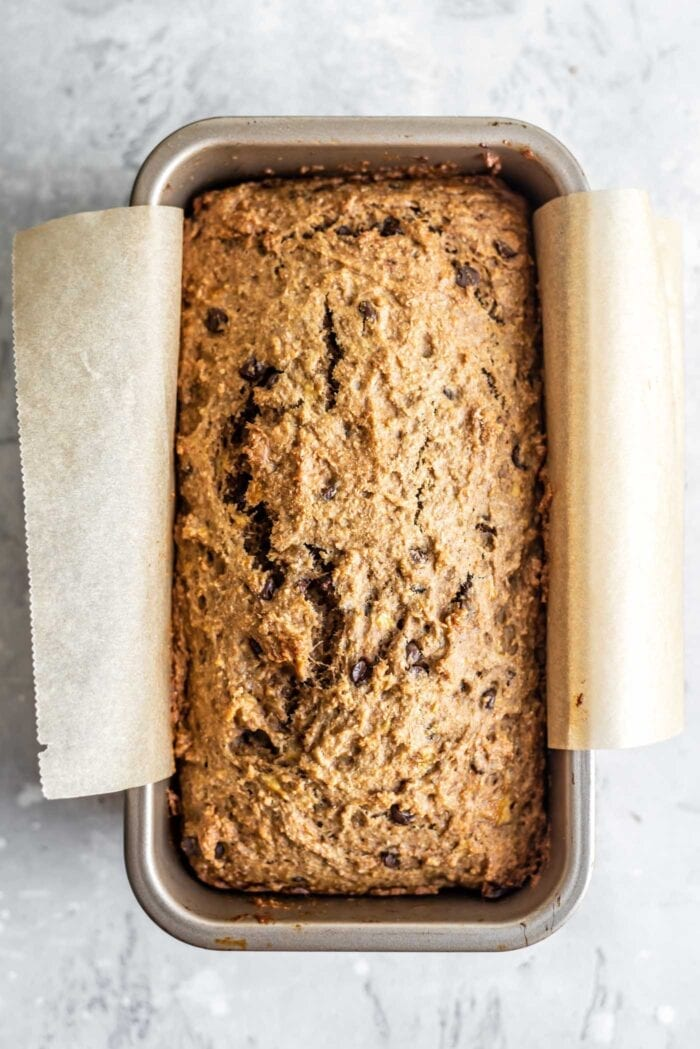 Fresh baked banana bread in a loaf pan lined with parchment paper.