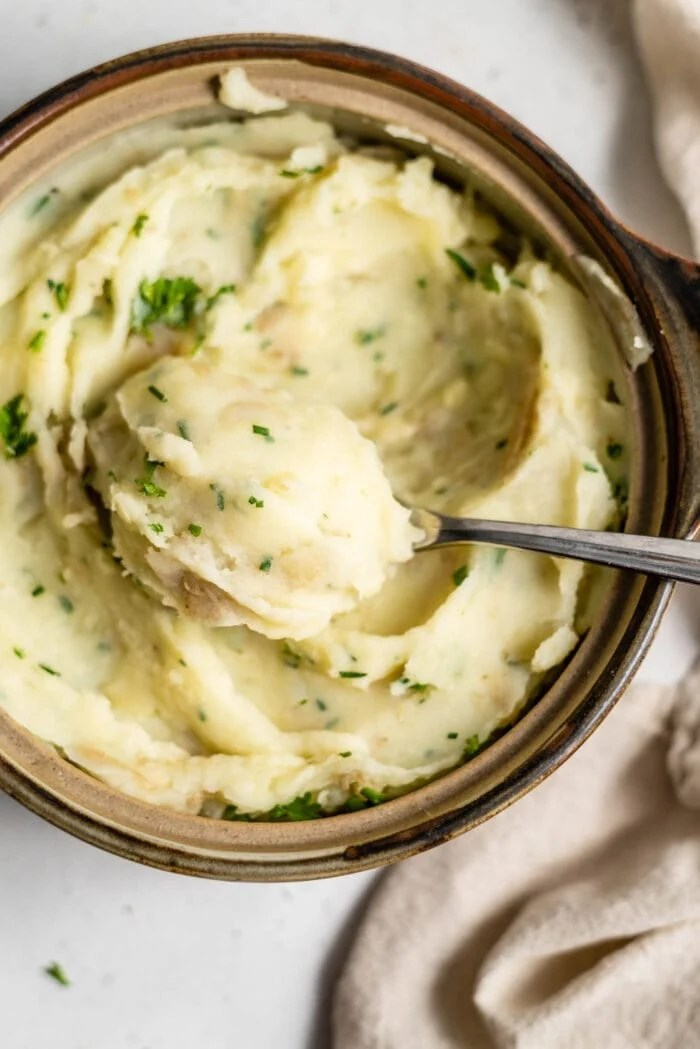 A spoon scooping a large spoonful of mashed potatoes out of a serving dish.