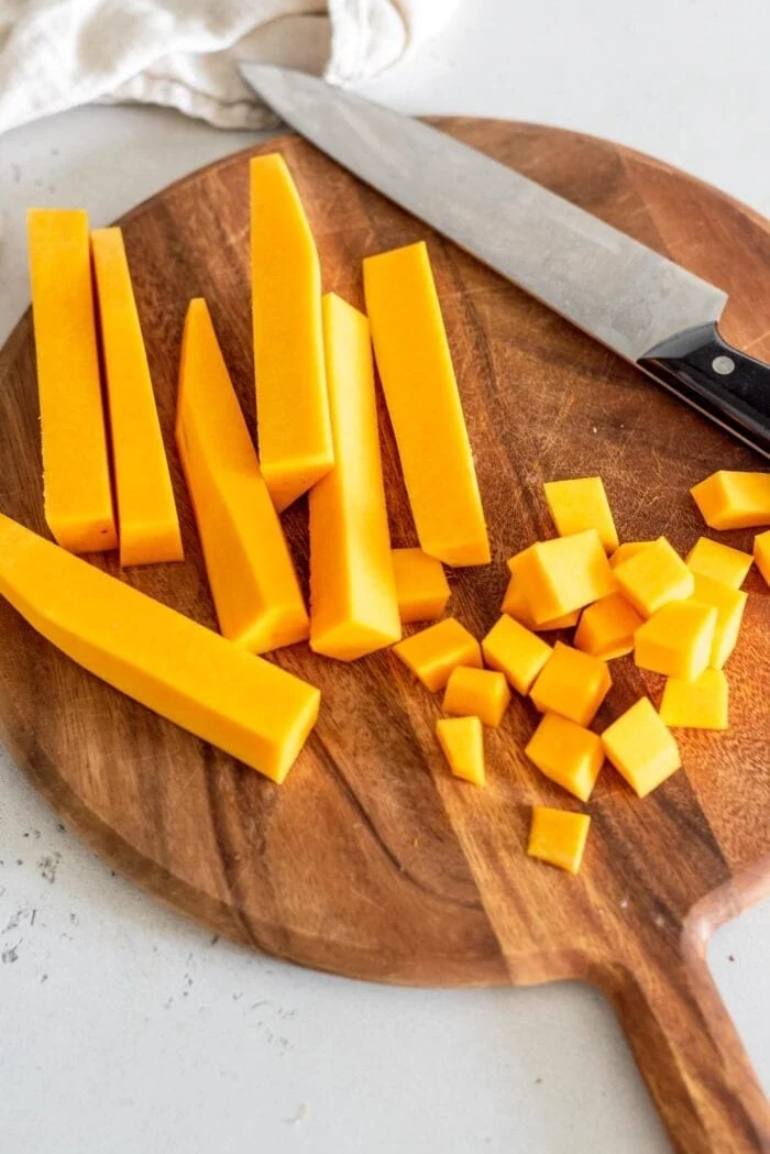 Peeled butternut squash chunks on a cutting board with a knife.