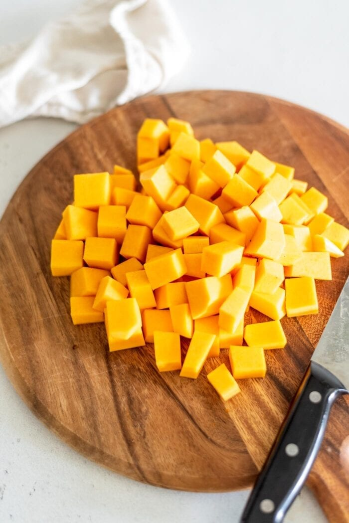 3 cups of peeled and cubed butternut squash on a cutting board with a knife.