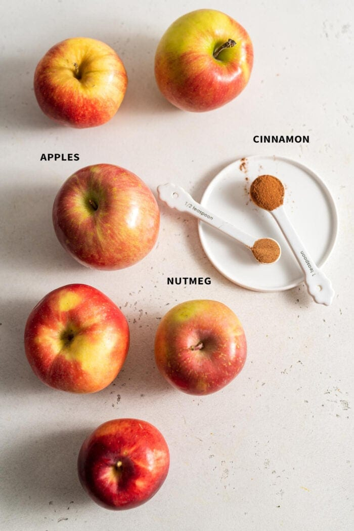6 apples, 1 tsp of cinnamon and 1/2 tsp of nutmeg on a white surface.