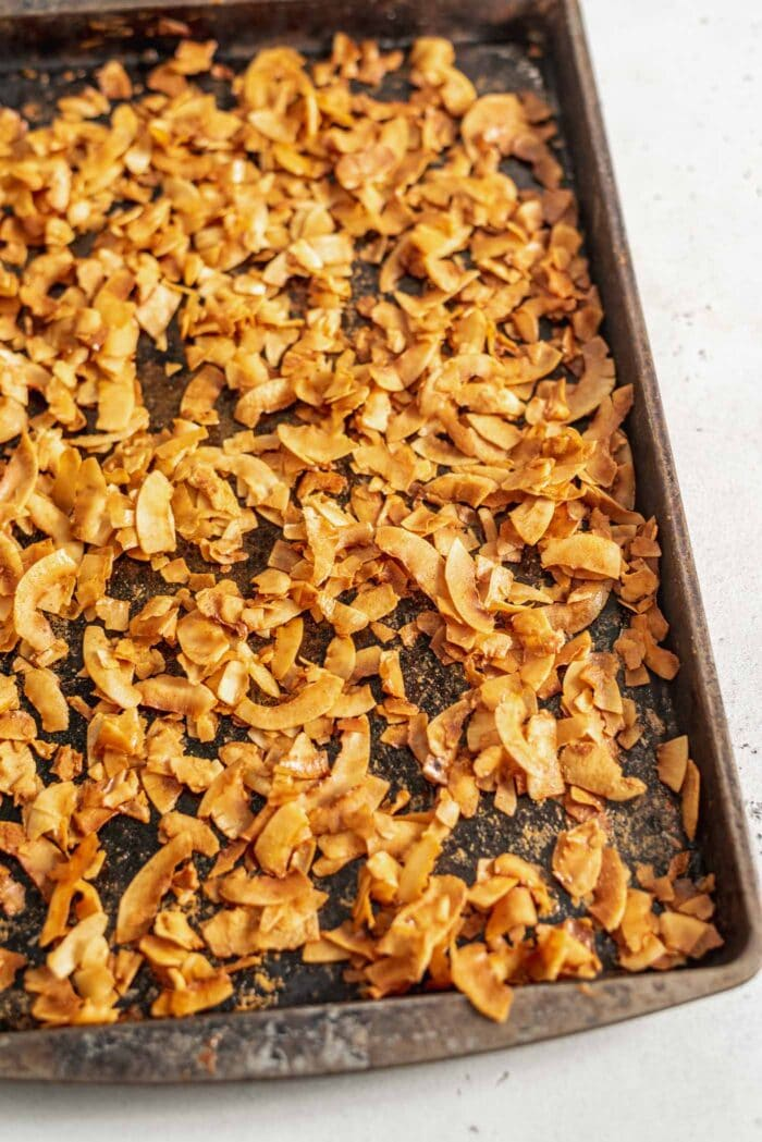 A baking tray full of golden brown coconut bacon.