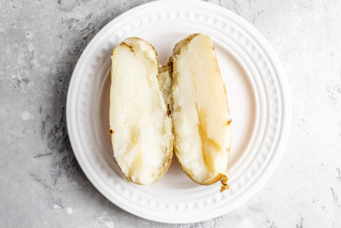 A sliced open baked Russet potato on a small white plate,