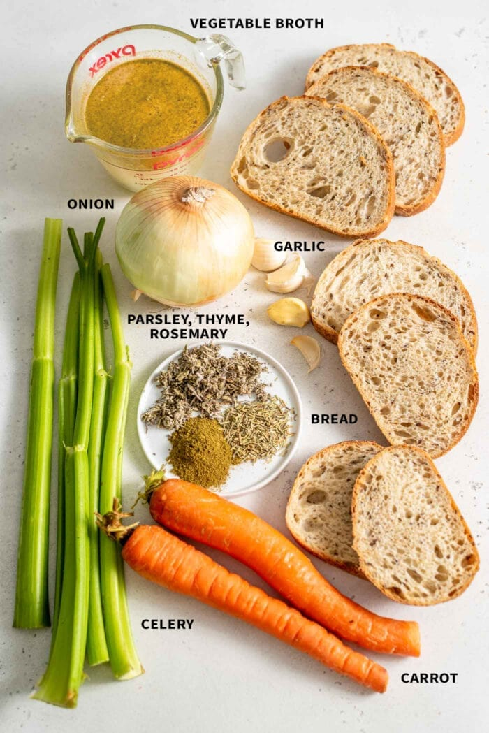 The ingredients for vegan stuffing: celery, carrots, bread, herbs, broth, garlic and onion, sitting on a white surface.