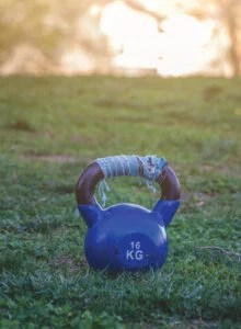 A blue kettlebell sitting in a grassy field.