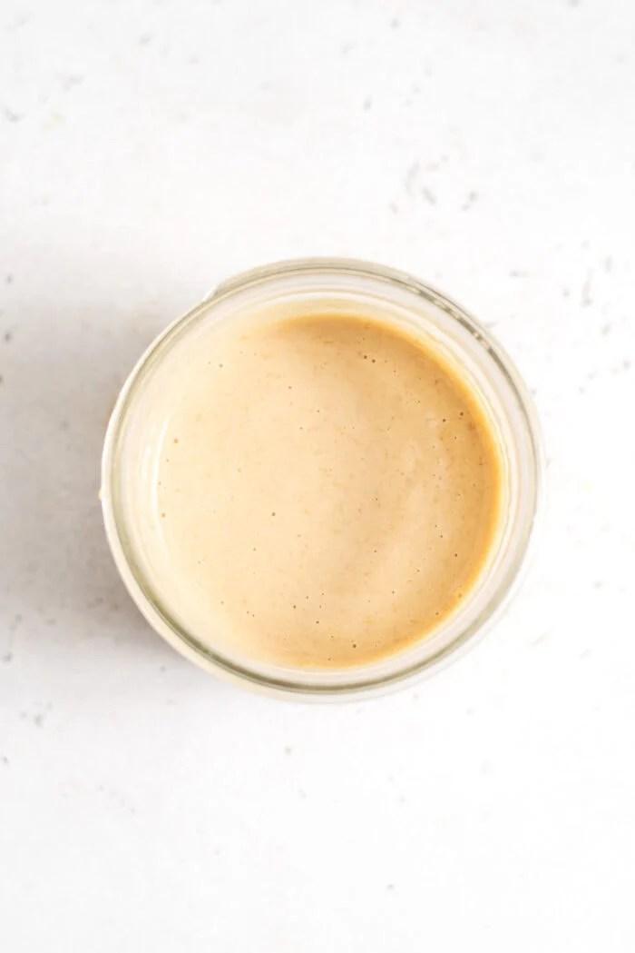 Creamy miso tahini dressing in a small glass jar.
