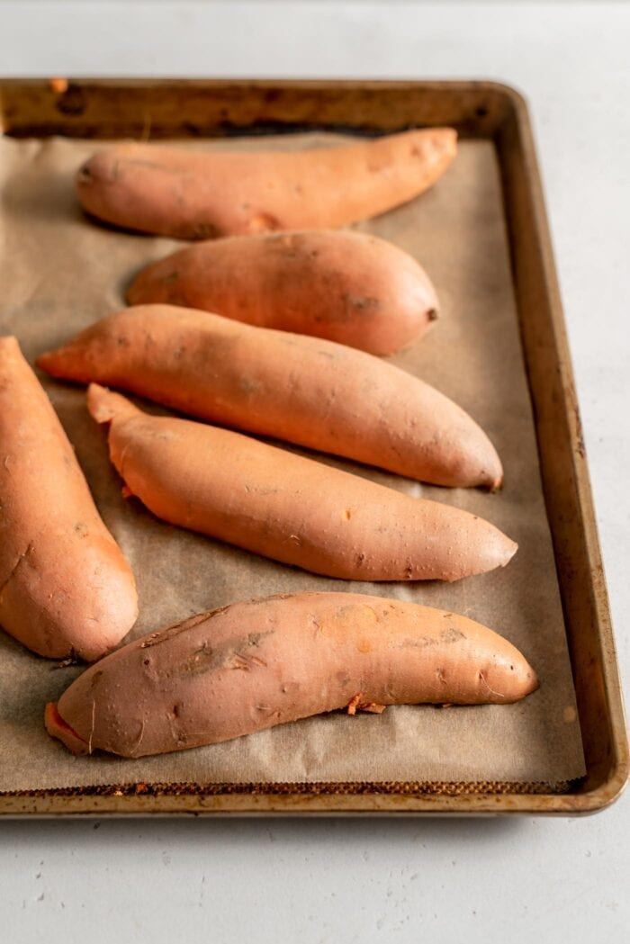 Sweet potatoes cut in half and placed face down on a baking tray lined with parchment paper.
